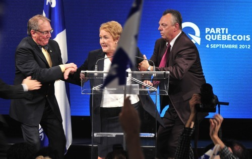 Parti Quebecois Leader Pauline Marois is whisked off stage as she delivered her victory speech in Quebec, Tuesday Sept. 4, 2012. With the win, Marois becomes the first female premier in Quebec history. Police were not immediately able to provide details but party organizers informed the crowd that there had been an explosive noise and they needed to clear the auditorium. Police say one man was arrested and two people were injured.  (AP Photo/Paul Chiasson, The Canadian Press)