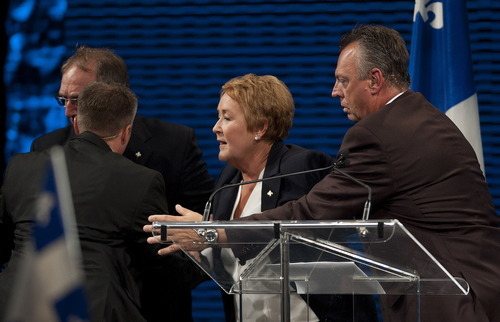 Parti Quebecois leader Pauline Marois is removed from the stage by police as she as she declares victory to supporters in Montreal, Tuesday, Sept. 4, 2012 following her election win. Police were not immediately able to provide details but party organizers informed the crowd that there had been an explosive noise and they needed to clear the auditorium. Police say one man was arrested and two people were injured. (AP Photo/Graham Hughes, The Canadian Press)