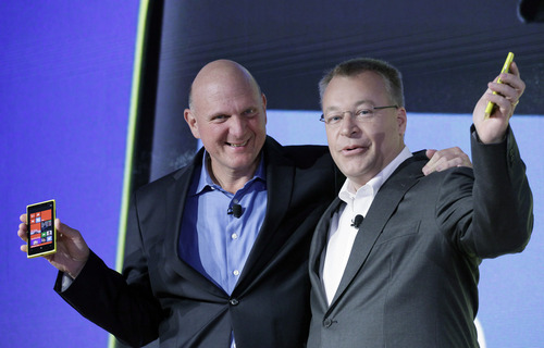 Steve Ballmer, left, Chairman and CEO of Microsoft, and Stephen Elop, President and CEO of Nokia, introduce Nokia's newest smartphone, the Lumia 920, equipped with Microsoft's Windows Phone 8, Wednesday, Sept. 5, 2012 in New York.  Nokia revealed its first smartphones to run the next version of Windows, a big step for a company that has bet its future on an alliance with Microsoft. (AP Photo/Mark Lennihan)