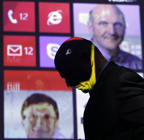 Steve Ballmer, CEO of Microsoft, walks past a projected display showing Bill Gates, lower left, and himself, during a discussion of Nokia's newest smartphone, the Lumia 920, equipped with Microsoft's Windows Phone 8, Wednesday, Sept. 5, 2012 in New York. Nokia revealed its first smartphones to run the next version of Windows Wednesday, a big step for a company that has bet its future on an alliance with Microsoft. (AP Photo/Mark Lennihan)