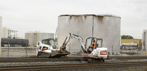Paul Fraughton   The Salt Lake Tribune Workers scoop up gravel  Friday, Aug. 31, 2012, around the railroad tracks in front of an oil storage tank that ruptured and spewed oil over a wide area of Woods Cross and Bountiful.