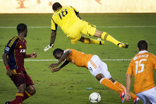 Real Salt Lake goalkeeper Nick Rimando (18) commits a penalty against Houston Dynamo forward Macoumba Kandji (9) in the penalty area during stoppage time of an MLS soccer match, Thursday, Sept. 6, 2012, in Houston. Houston's Colin Clark converted the penalty kick for a 1-0 win. (AP Photo/Houston Chronicle, Smiley N. Pool)  MANDATORY CREDIT