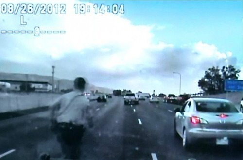 Davis County Sheriff's Deputy Matthew Boucher runs to stop a car with an unconscious driver on Interstate 15. (Davis County Sheriff's Office photo)