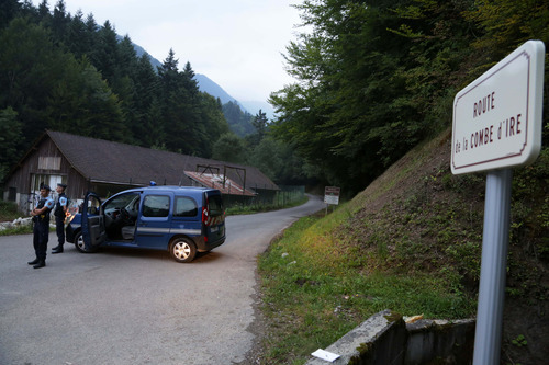 Gendarmes block access to a killing site near Chevaline, French Alps, Wednesday Sept. 5, 2012.  French authorities say at least four people have been shot to death in a forest in the Alps.An official with the regional administration for the Haute-Savoie region says three of the bodies were found in a BMW registered in Britain. (AP Photo/Alexis Moro)
