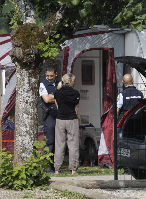 Gendarmes and investigators stand at the camp where the slain British family were holidaying in a camp site of Saint Jorioz, near Annecy, Thursday, Sept. 6, 2012. A 4-year-old British girl hid for eight hours beneath the bodies of slain family members in the back of their car in a nearby forest, before she was discovered by French investigators who had been guarding the vehicle, a prosecutor said Thursday. Three people, a man and two women, had been shot to death, as was a French cyclist whose body was found nearby.  (AP Photo/Lionel Cironneau)