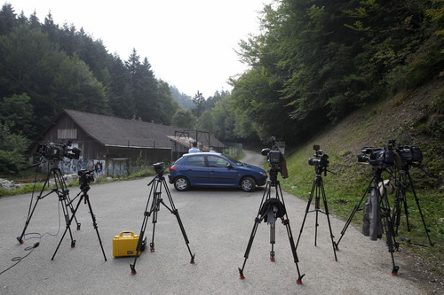 Cameras are seen in front of Gendarmes who blocks access to a site where people were shot to death near Chevaline, French Alps, Thursday Sept. 6, 2012. A 4-year-old British girl hid for eight hours beneath the bodies of slain family members in the back of their car before she was discovered by French investigators who had been guarding the vehicle, a prosecutor said Thursday. Three people — a man and two women — had been shot to death, as was a French cyclist whose body was found nearby.  (AP Photo/Laurent Cipriani)