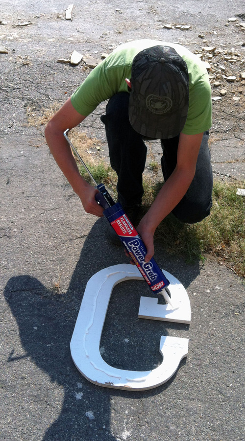 Quinn Argyle, 15, has undertaken an Eagle Scout project of restoring the goat barn on the Utah State Fairpark.  Here he prepares the letter G for the outside sign for the barn. Courtesy of Argyle family