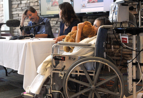 Seven-year-old Sierra Jane Downing from Pagosa Springs, Colo., hugs her teddy bear while her father Sean Downing and mother Darcy Downing talk about her recovery from Bubonic Plague at the Rocky Mountain Hospital for Children at Presbyterian/St. Luke's during a news conference Wednesday, Sept. 5, 2012, in Denver. It is believed Downing caught the Bubonic Plague from burying a dead squirrel. (AP Photo/Jack Dempsey)