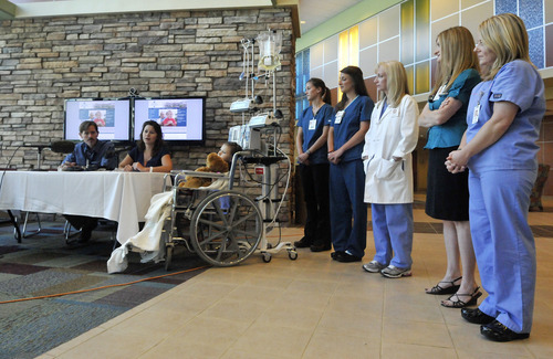 Seven-year-old Sierra Jane Downing from Pagosa Springs, Colo., looks on while surrounded by the medical staff and parents Sean and Darcy Downing during a news conference talking about her recovery from Bubonic Plague at the Rocky Mountain Hospital for Children at Presbyterian/St. Luke's Wednesday, Sept. 5, 2012, in Denver. It is believed Downing caught the Bubonic Plague from burying a dead squirrel. (AP Photo/Jack Dempsey)