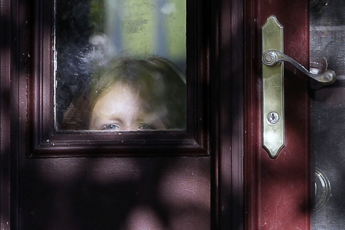 A child peers through the window on a door of Drew Peterson's house on Thursday, Sept. 6, 2012., in Bolingbrook, Ill. Retired Bolingbrook police officer Drew Peterson has been found guilty of murdering his third wife, Kathleen Savio. State's Atty. James Glasgow says he has not ruled out charging Peterson with the death of Peterson's fourth wife, Stacy, who has been missing since 2007. (AP Photo/Nam Y. Huh)