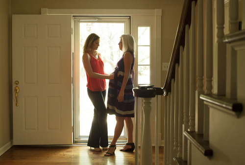 Emily Jordan, left, examines the pregnant belly of her mother Cindy Reutzel on Sunday, Aug. 19, 2012 in Naperville, Ill. After Jordan underwent a radical hysterectomy, she and her husband took up an offer from Reutzel to act as a surrogate for their child. (AP Photo/Sitthixay Ditthavong)