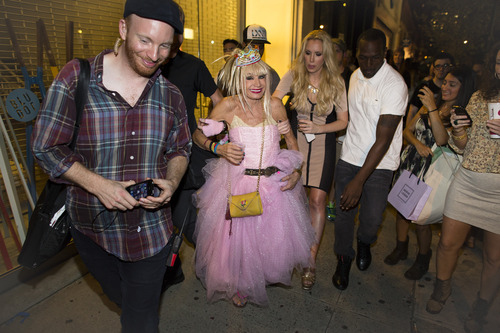Designer Betsey Johnson walks the street during Fashion's Night Out in Manhattan's SoHo neighborhood, Thursday, Sept. 6, 2012, in New York. Fashion's Night Out is a global event created to restore consumer confidence and boost the economy of the fashion industry. (AP Photo/John Minchillo)