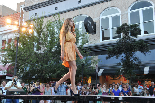 A model struts along the catwalk located on Broughton Street in front of 24e Thursday evening Sept. 6, 2012 during Savannah's Second Fashion's Night Out in Savannah, Ga. Clothing from local retailers in the downtown area was highlighted during the event. (AP Photo/The Morning News, Richard Burkhart)
