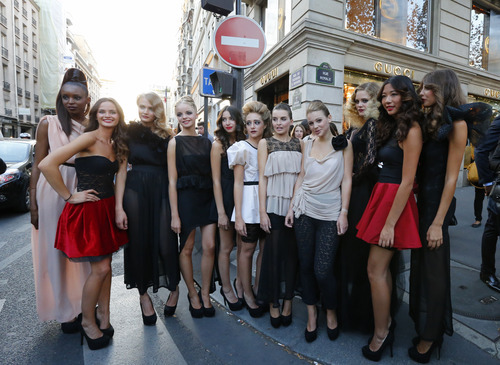Models pose on the streets of Paris, Thursday Sept. 6 2012, during Fashion's Night Out where fashion shops open their doors at night  to encourage consumers to support the fashion industry. (AP Photo/Jacques Brinon)