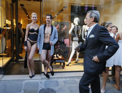Models pose in front of a fashion shop on the streets of Paris, Thursday Sept. 6 2012, during Fashion's Night Out where fashion shops open their doors at night  to encourage consumers to support the fashion industry. (AP Photo/Jacques Brinon)