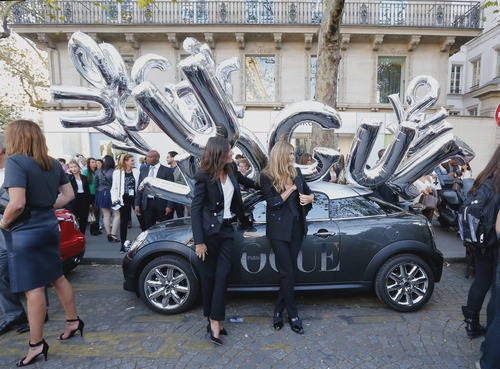 Fashion models pose in the streets of Paris, with balloons Thursday Sept. 6 2012, during Fashion's Night Out where fashion shops open their doors at night  to encourage consumers to support the fashion industry. (AP Photo/Jacques Brinon)