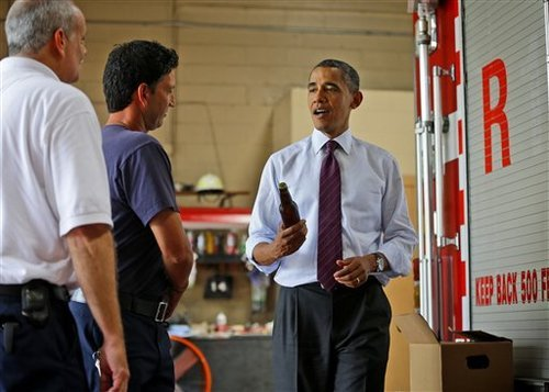 President Barack Obama holds up a bottle of beer as he delivers a case of White House brewed beer to the firefighters at Fire Station No. 14, during an unscheduled stop, Tuesday, Sept. 4, 2012, in Norfolk, Va. (AP Photo/Pablo Martinez Monsivais)