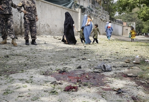 Afghans pass the scene of a suicide attack as they walk to their house in Kabul, Afghanistan, Saturday, Sept. 8, 2012. A suicide bomber blew himself up near NATO headquarters in the Afghan capital on Saturday, killing at least six people, police said. (AP Photo/Musadeq Sadeq)