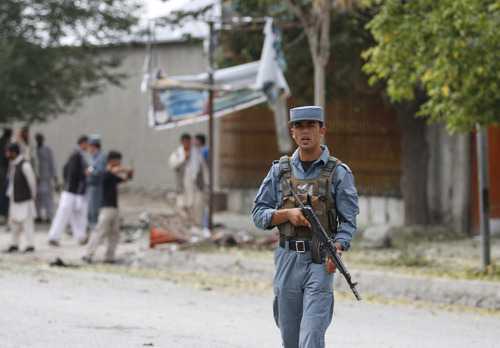 An Afghan policeman stands guard at the scene of a suicide bombing in Kabul Afghanistan, Saturday, 8, 2012. Afghan authorities say a suicide bomber has blown himself up near NATO headquarters in Kabul, killing at least 6 people (AP Photo/Ahmad Jamshid)