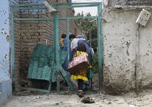 Afghan children with adults pass through the damaged door of their house following a suicide attack in Kabul, Afghanistan, Saturday, Sept. 8, 2012. A suicide bomber blew himself up near NATO headquarters in the Afghan capital on Saturday, killing at least six people, police said. (AP Photo/Musadeq Sadeq)