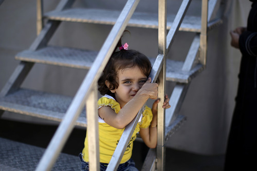 In this Friday, Sept. 7, 2012 photo, a Syrian girl, who fled his home with her family due to fighting between the Syrian army and the rebels, waits to be seen by a doctor outside a makeshift clinic, at the Bab Al-Salameh border crossing where he and his family take refugee in hopes of entering one of the refugee camps in Turkey, near the Syrian town of Azaz. Despite rising international concern and new pledges of aid, the plight of Syria's internally displaced is growing worse as fighting shows no signs of slackening and more head for the borders. Syria's neighbors are reluctant to take in more refugees, leaving thousands, at least half young children, stranded on the borders with poor hygiene and insufficient food. At the Bab al-Salameh border crossing there are already an estimated 5,000 refugees hoping to cross into Turkey, which already hosts 80,000 Syrians and isn't allowing more in for now. (AP Photo/Muhammed Muheisen)