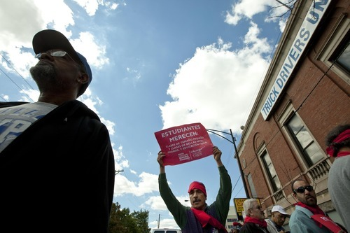 Socorro Pizaña, centre, a janitor at Dirksen School, holds a sign supporting teachers in front of a building the Chicago Teachers Union has designated its strike headquarters on Saturday, Sept. 8, 2012 in Chicago. The union has vowed to strike on Monday, Sept. 10, 2012, should it fail to reach an agreement over teachers' contracts with Chicago Public Schools by  that date. (AP Photo/Sitthixay Ditthavong)