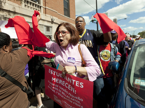 Teachers and pro-teacher community groups rally in front of a building the Chicago Teachers Union has designated its strike headquarters on Saturday, Sept. 8, 2012 in Chicago. The union has vowed to strike on Monday, Sept. 10, 2012 if an agreement over teachers' contracts is not reached with Chicago Public Schools by  Monday. (AP Photo/Sitthixay Ditthavong)