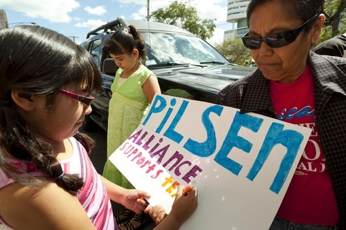 Eight-year-old TaliSol Medina, left, a third-grader from Galileo School, puts the finishing touches on a pro-teachers poster for the Pilsen Alliance community group in front of the Chicago Teachers Union strike headquarters on Saturday, Sept. 8, 2012 in Chicago. The union has vowed to strike on Monday, Sept. 10, 2012 if an agreement over teachers' contracts is not reached with Chicago Public Schools by  Monday. (AP Photo/Sitthixay Ditthavong)