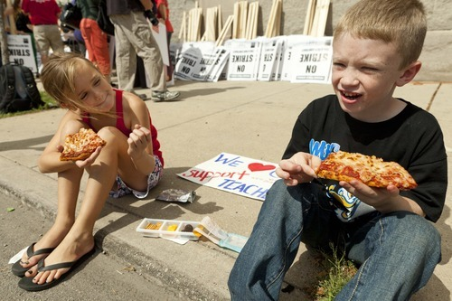 Young children eat pizza as their parents organize strike signage at the Chicago Teachers Union strike headquarters on Saturday, Sept. 8, 2012 in Chicago. The union has vowed to strike on Monday, Sept. 10, 2012, should it fail to reach an agreement over teachers' contracts with Chicago Public Schools by  that date. (AP Photo/Sitthixay Ditthavong)