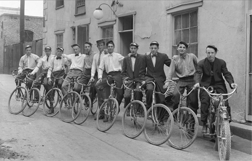 Image shows a group of messenger boys lined up on their bicycles, posing for a photograph, June 27, 1912. Courtesy of Utah Historical Society