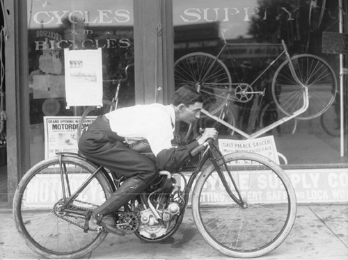 Image shows a man sitting on an antique motorcycle in front of a bicycle and motorcycle shop, May 28, 1910. Courtesy of Utah Historical Society