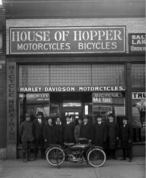 Image shows a group of men standing in front of the House of Hopper motorcycle and bicycle shop on 300 South, January 25, 1919. They are showing off a brand new motorcycle. Courtesy of Utah Historical Society