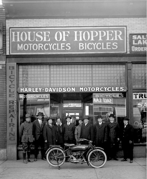 Image shows a group of men standing in front of the House of Hopper motorcycle and bicycle shop on 300 South, Jan. 25, 1919. They are showing off a brand new motorcycle. Courtesy of Utah Historical Society