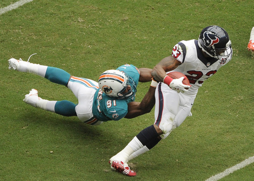 Miami Dolphins linebacker Cameron Wake (91) is dragged by Houston Texans running back Arian Foster (23) in the first quarter of an NFL football game on Sunday, Sept. 9, 2012, in Houston. (AP Photo/Dave Einsel)