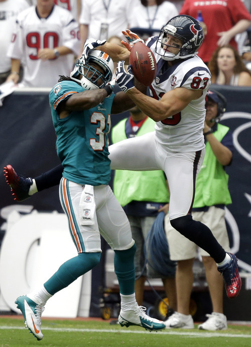 Houston Texans wide receiver Kevin Walter (83) reaches for a pass as Miami Dolphins defensive back Richard Marshall (31) defends in the second quarter of an NFL football game on Sunday, Sept. 9, 2012, in Houston. Marshall was called for pass interference on the play. (AP Photo/Eric Gay)