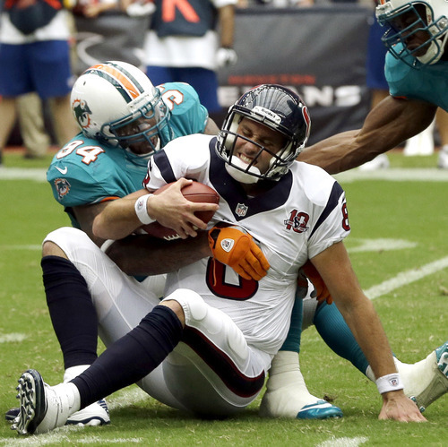 Houston Texans quarterback Matt Schaub (8) is sacked by Miami Dolphins defensive tackle Randy Starks (94) and linebacker Cameron Wake, right, in the second quarter of an NFL football game, Sunday, Sept. 9, 2012, in Houston. (AP Photo/David J. Phillip)