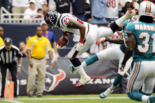 Houston Texans running back Arian Foster (23) leaps into the end zone for a touchdown as Miami Dolphins defensive back Chris Clemons, right, tries to tackle him in the second quarter of an NFL football game, Sunday, Sept. 9, 2012, in Houston. (AP Photo/Dave Einsel)