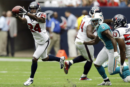 Houston Texans cornerback Johnathan Joseph intercepts a pass as Miami Dolphins wide receiver Legedu Naanee watchesn in the second quarter of an NFL football game, Sunday, Sept. 9, 2012, in Houston. (AP Photo/David J. Phillip)
