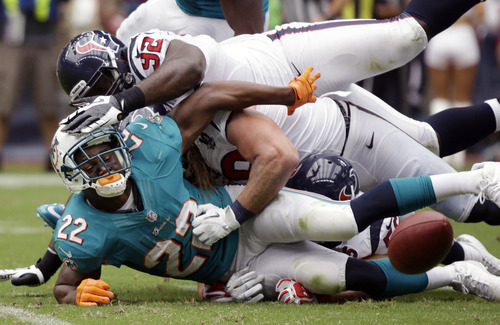 Miami Dolphins running back Reggie Bush (22) fumbles the ball after being tackled by Houston Texans' Earl Mitchell (92) and Brooks Reed, center, in the first quarter of an NFL football game on Sunday, Sept. 9, 2012, in Houston. (AP Photo/Eric Gay)