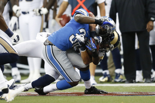 Detroit Lions running back Kevin Smith (30) is tackled by St. Louis Rams linebacker James Laurinaitis during the first half of an NFL game in Detroit, Sunday, Sept, 9, 2012. (AP Photo/Rick Osentoski)