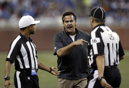 St. Louis Rams head coach Jeff Fisher, center, yells at side judge Paul Caldera, right, as referee Donovan Briggans, left, listens in the second quarter of an NFL football game against the Detroit Lions in Detroit, Sunday, Sept. 9, 2012. (AP Photo/Paul Sancya)