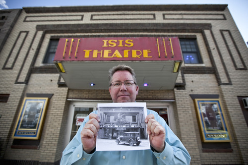 In this photo from Sept. 4, 2012, Thom Reeves, owner of the Isis theatre, holds a photo showing the building's facade in 1932 during the showing of the movie