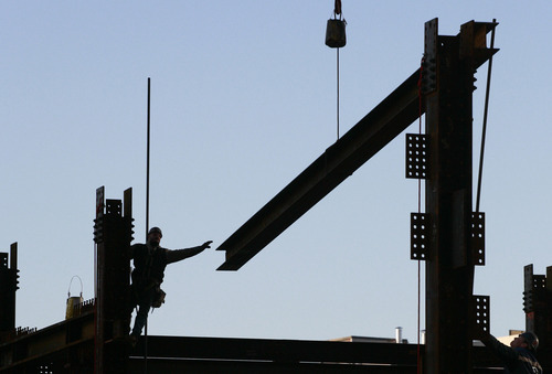 FILE - In this file photo of Jan. 27, 2010, an ironworker reaches for a beam suspended from a crane at One World Trade Center, in New York. Eleven years after terrorists attacked the World Trade Center, the new World Trade Center now dominates the lower Manhattan skyline. (AP Photo/Mark Lennihan, File)