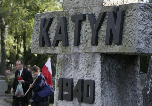 People walk with a Polish flag near a memorial to the victims of Katyn, the Soviet massacre of 22,000 Polish officers in 1940, in Warsaw, Poland on Monday, Sept. 10, 2012. On Monday the U.S. National Archives is releasing about 1,000 newly declassified documents related to Katyn. Some shed further light on decades of suppression of Soviet guilt within the U.S. government. The cover-up began during World War II when the U.S. needed the Soviets to defeat Germany and Japan, and continued on some level long after. (AP Photo/Czarek Sokolowski)