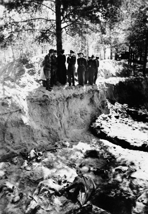 FILE - In this May 1943 file photo, a group of American and British POWs being held by the Germans, including Lt. Col. John H. Van Vliet Jr. and Capt. Donald B. Stewart, look over a mass grave where murdered Polish officers are buried, near Smolensk, Russia. The Soviet secret police killed the Poles in 1940, hoping to eliminate an elite that would have resisted Soviet control of Poland. Van Vliet and Stewart were among a group of British and American prisoners forced to see the horrifying site by the Germans, who wanted word to get out to the world of the Soviet atrocity. Newly declassified documents being opened to the public on Monday, Sept. 10, 2012, by the U.S. National Archives show that Van Vliet and Stewart sent coded messages to Washington after their visit saying they believed the German account of Soviet guilt. It is credible evidence that Washington had relatively early on, but of which it still chose to ignore in order not to jeopardize the alliance with Joseph Stalin. (AP Photo/File)