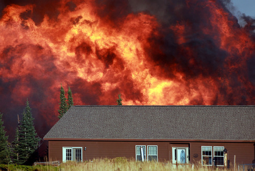 A wildfire burns near a home Sunday, Sept. 9, 2012 on Casper Mountain in Casper, Wyo. Residences and campgrounds were evacuated as the uncontained wildfire spread across the southeast portion of the mountain. (AP Photo/The Casper Star-Tribune, Alan Rogers)