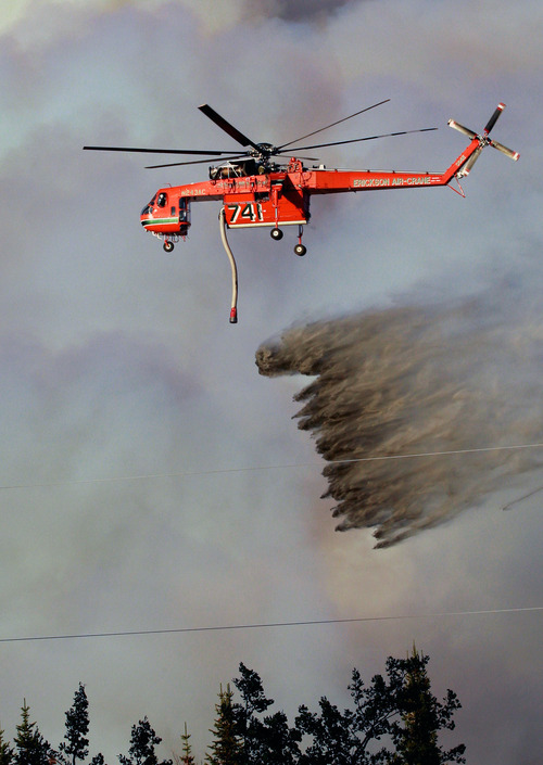 A plane drops fire retardant on a wildfire Sunday, Sept. 9, 2012 on Casper Mountain in Casper, Wyo. Residences and campgrounds were evacuated as the uncontained wildfire spread across the southeast portion of the mountain. (AP Photo/The Casper Star-Tribune, Alan Rogers)