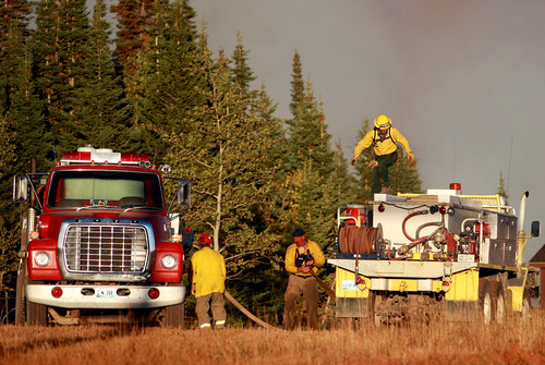 Firefighters refill their brush truck from a water tender while battling a wildfire Sunday, Sept. 9, 2012 on Casper Mountain in Casper, Wyo. Residences and campgrounds were evacuated as the uncontained wildfire spread across the southeast portion of the mountain. (AP Photo/The Casper Star-Tribune, Alan Rogers)