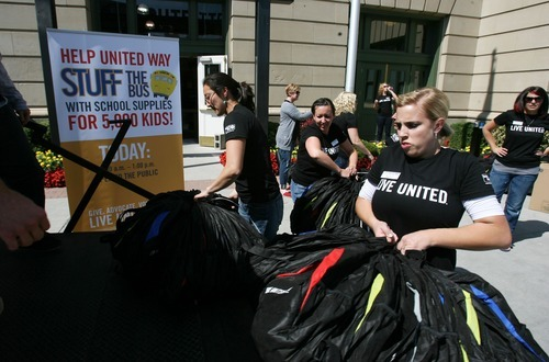 Steve Griffin  |  The Salt Lake Tribune United Way employees load backpacks onto a Granite School District truck last year at The Gateway as part of the United Way's Stuff the Bus project. Donated school items were given to Utah schoolchildren.