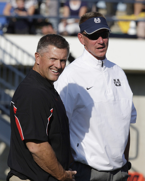 Utah coach Kyle Whittingham, left, and Utah State coach Gary Andersen talk before an NCAA college football game Friday, Sept. 7, 2012, in Logan, Utah, (AP Photo/Rick Bowmer)